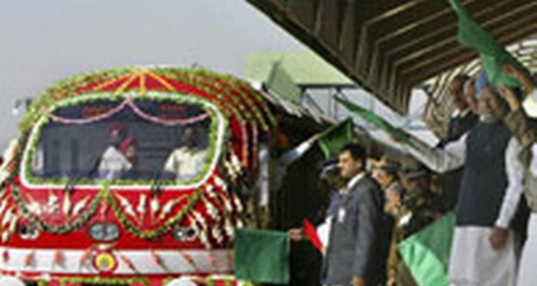 हरी झंडी दिखाकर रेल को रवाना करते मनमोहन सिंह।