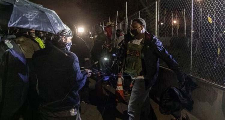 अमेरिका के मिनियापोलिस शहर में फायरिंग के विरोध में प्रदर्शन करते लोग।