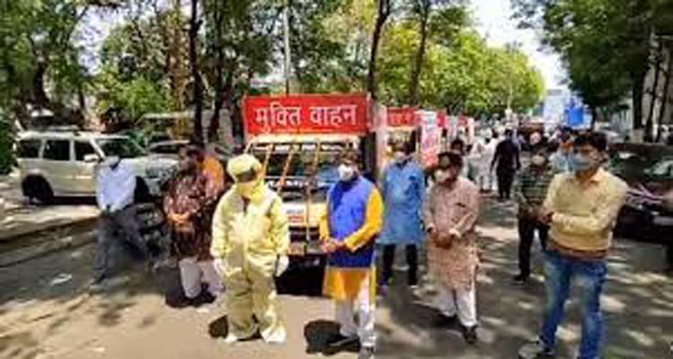 एक व्यक्ति को पीपीई किट पहनाकर फोटो खिंचवाते आलोक शर्मा